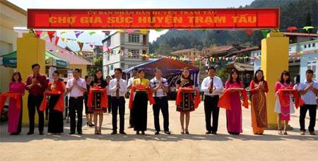 Các đồng chí lãnh đạo cắt băng khánh thành Chợ gia súc huyện Trạm Tấu.
