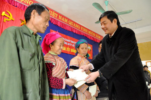 Lãnh đạo đại diện Văn phòng Báo Công an thành phố Hồ Chí Minh trao quà cho các hộ nghèo xã Nà Hẩu (Văn Yên).