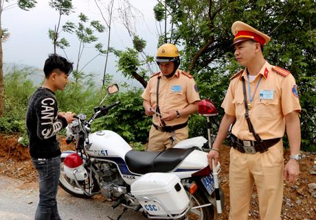 Lực lượng CSGT Công an huyện Văn Chấn kiểm tra giấy tờ của người điều khiển phương tiện tham gia giao thông.