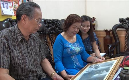 Ông Trần Huy Ân và nghệ sỹ Khánh Nguyệt xem bức ảnh ông Ân vinh dự lên tặng hoa Bác Hồ.