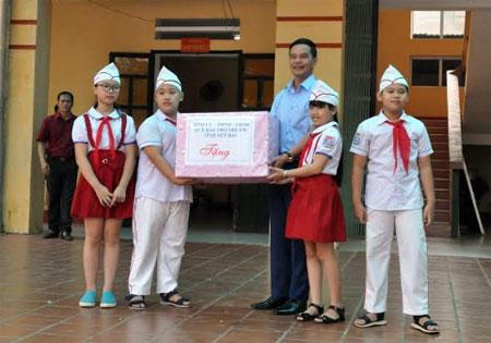 Đồng chí Dương Văn Tiến trao quà Trung thu cho các em học sinh Trường Tiểu học Nguyễn Thái Học, thành phố Yên Bái.