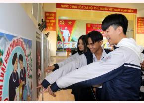 Các em học sinh Trường THPT Chuyên Nguyễn Tất Thành xem tranh cổ động tại Triển lãm.
