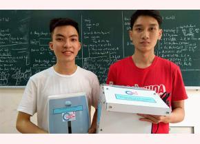 Sinh viên Dương Thế Long (trái) và Lưu Văn Thạo (phải) cùng hai phiên bản của máy rửa tay tự động.