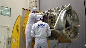 Các kỹ sư Cơ quan Hàng không Vũ trụ Nhật Bản (JAXA) đang lắp đặt thử nghiêm vệ tinh vào bộ gá đặt trong tên lửa.