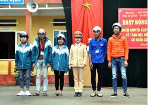 Chi đoàn Công an huyện Trấn Yên tặng mũ bảo hiểm cho các em học sinh.