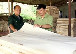 Cựu chiến binh Nguyễn Minh Tiến (bên phải) kiểm tra sản xuất ván bóc tại xưởng chế biến.