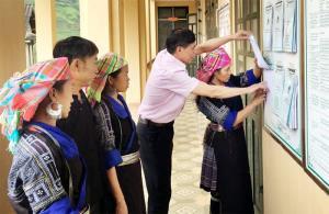 Cán bộ Phòng Giao dịch Ngân hàng Chính sách xã hội huyện Mù Cang Chải hướng dẫn người dân làm thủ tục vay vốn.