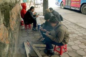 Người dân trên phố Trần Khánh Dư đốt củi để sưởi ấm.