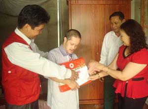 Đại diện Hội Chữ thập đỏ tỉnh Yên Bái tặng quà, động viên nạn nhân Nguyễn Hồng Văn, thị trấn Yên Thế.