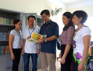 Đồng chí Nguyễn Huy Cường - Giám đốc Sở Tư pháp (người đứng giữa) trao đổi với cán bộ Phòng Phổ biến, giáo dục pháp luật  về công tác xây dựng tủ sách pháp luật ở cơ sở.
