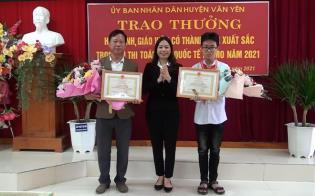 Đồng chí Lã Thị Liền -Phó Chủ tịch UBND huyện Văn Yên tặng hoa và trao thưởng cho thầy giáo Trần Phi Hùng và em Trần Quốc Thái.