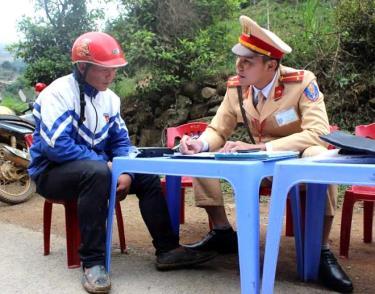 Thượng úy Lê Xuân Trường tuyên truyền pháp luật về an toàn giao thông cho người dân trong quá trình thực hiện nhiệm vụ.