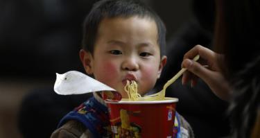 Một em bé người Trung Quốc được mẹ đút ăn mì gói - Ảnh: REUTERS