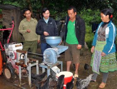 Vợ chồng anh Mùa A Dơ (đứng bên phải) giới thiệu chiếc máy nghiền ngô làm thức ăn cho gia súc.
