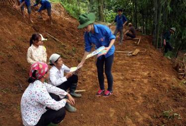 Phạm Thị Phương phát tờ rơi tuyên truyền pháp luật cho bà con tại xã Chấn Thịnh, huyện Văn Chấn.
