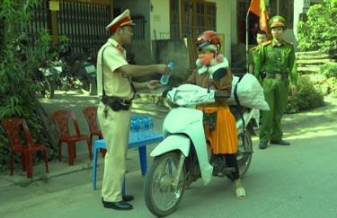 Cảnh sát giao thông Công an huyện Trạm Tấu phát nước miễn phí cho người dân.