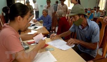 Người dân nhận tiền hỗ trợ khó khăn do dịch COVID-19.