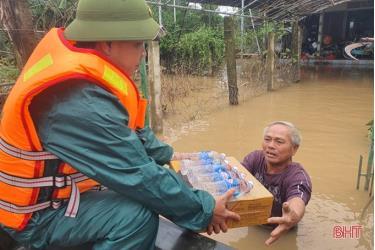 Những hộ dân đang mắc kẹt do ngập lũ nặng lội ra nhận tiếp tế lương thực, nước uống tại xã Cẩm Duệ, huyện Cẩm Xuyên, tỉnh Hà Tĩnh.