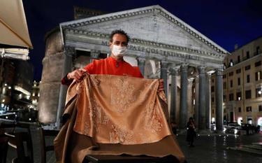 Nhân viên phục vụ bàn đeo khẩu trang dọn dẹp một quán bar trước cửa đền thờ Pantheon nổi tiếng tại Rome (Italia).