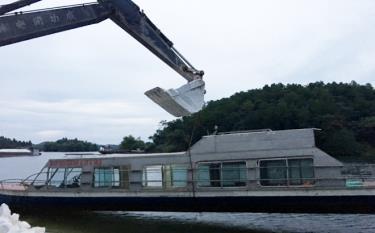 Chiếc tàu thủy được cẩu lên khỏi mặt nước chuẩn bị lên xe vào cứu hộ đồng bào miền Trung