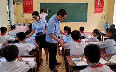 Cán bộ Bảo hiểm xã hội huyện Yên Bình phát tờ rơi tuyên truyền chính sách BHYT tại Trường Tiểu học và THCS xã Hán Đà.