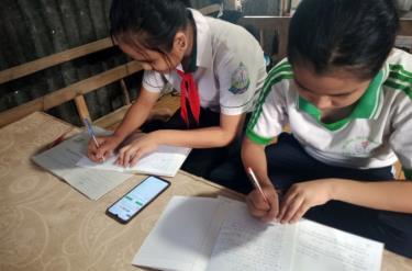Hai chị em (lớp 6 và 8) cùng một nhà ở Cần Thơ học online chung trên điện thoại di động của mẹ.