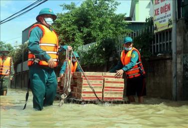 Lực lượng chức năng vận chuyển nhu yếu phẩm hỗ trợ các hộ dân bị ngập nước tại xã Quỳnh Hồng, huyện Quỳnh Lưu, Nghệ An, ngày 27/9/2021.