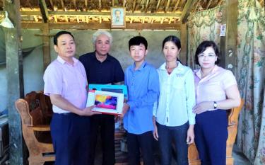 Ông Nguyễn Văn Bằng trao máy tính bảng cho cháu Nguyễn Tiến Mạnh, bản Chao, xã Việt Hồng, huyện Trấn Yên.