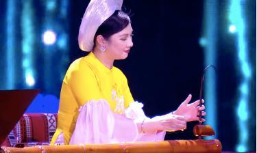 NSƯT đàn bầu Việt Nam Lệ Giang nổi bật với tà áo dài màu vàng.
