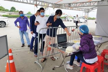 Người dân xếp hàng chờ kiểm tra giấy tờ để qua chốt ở Hà Nội