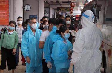 Các công dân Yên Bái trở về tỉnh từ các tỉnh miền Nam tại Cảng hàng không quốc tế Nội Bài, được kiểm tra thân nhiệt trước khi lên xe về khu cách ly. (Ảnh: Minh Tuấn)