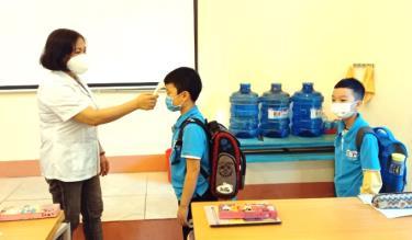 Học sinh trường Tiểu học Supe, huyện Lâm Thao, được đo thân nhiệt khi đến trường học trực tiếp.