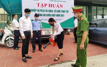 Cán bộ, chiến sĩ Công an tỉnh hướng dẫn nhân viên Chi nhánh Vietcombank Yên Bái thực hành sử dụng bình bọt chữa cháy.
