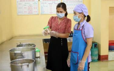 Cán bộ quản lý Trường Mầm non Yên Phú, huyện Văn Yên kiểm tra, lấy mẫu lưu thực phẩm trước khi chia suất ăn cho học sinh.
