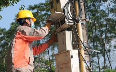 Công nhân Điện lực Văn Yên kiểm tra, lắp đặt công tơ mới cho khách hàng.