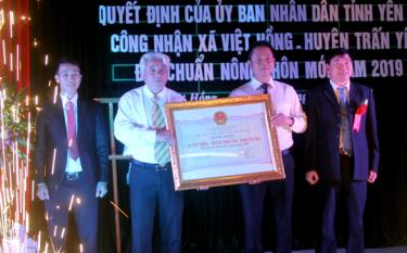 Thừa quyền của Chủ tịch UBND tỉnh Yên Bái, đồng chí Nguyễn Phúc Cường - Phó Giám đốc Sở Nông nghiệp và Phát triển nông thôn trao bằng công nhận đạt chuẩn NTM cho lãnh đạo xã Việt Hồng, huyện Trấn Yên.