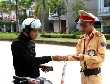 Cảnh sát giao thông huyện Yên Bình kiểm tra giấy tờ người điều khiển phương tiện tham gia giao thông.