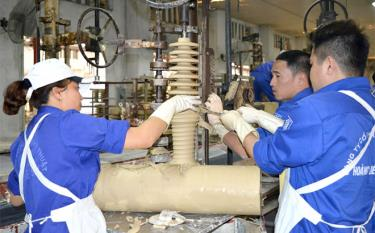 Workers at the Hoang Lien Son Ceramic Technical joint Stock Company make porcelain insulators.