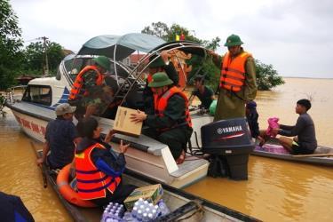 Cán bộ, chiến sĩ LLVT tỉnh Quảng Bình vượt lũ hỗ trợ lương thực cho người dân xã Tân Ninh, huyện Quảng Ninh. Ảnh: qdnd.vn