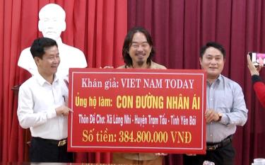 Journalist Truong Nguyen (C), owner of the Vietnam Today YouTube channel, presents the token of the donation for building the concreate road in De Cho.