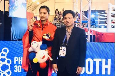 Phó Chủ tịch UBND thành phố Hà Nội Ngô Văn Quý (phải) chia vui với võ sĩ Nguyễn Thị Tâm.
