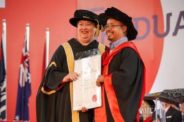 Alăng Thớ (bên phải) nhận bằng Tiến sĩ Quản trị nhân lực