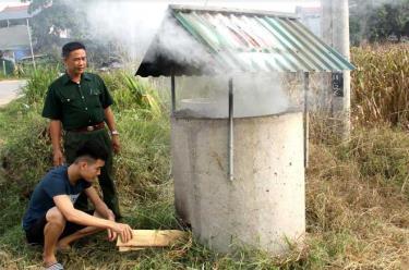 Chủ tịch Hội Cựu chiến binh Khương Văn Thịnh hướng dẫn người dân thôn Cầu Quạnh cách đốt rác trong bể.