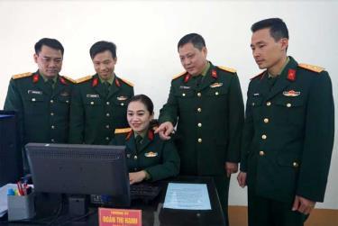 Thượng tá Trần Xuân Hướng - Trưởng ban Khoa học Quân sự Bộ CHQS tỉnh trao đổi nghiệp vụ công tác quản trị mạng với Thượng úy Đoàn Thị Hạnh và cán bộ chiến sĩ trong đơn vị.