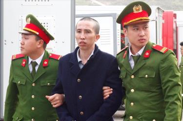 Kẻ bắt cóc, cưỡng hiếp, sát hại nữ sinh giao gà - Bùi Văn Công (áo đen) khi bị dẫn giải vào phiên tòa xét xử lưu động tại Sân vận động thành phố Điện Biên Phủ.