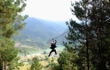 Một nam du khách vừa trượt zipline vừa cầm điện thoại quay chụp.