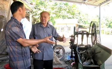 Ông Vũ Hữu Lê trao đổi với ông Trần Hồng Quân ở thôn Khe Dứa, xã Viễn Sơn, huyện Văn Yên về cách sử dụng máy băm cành quế.
