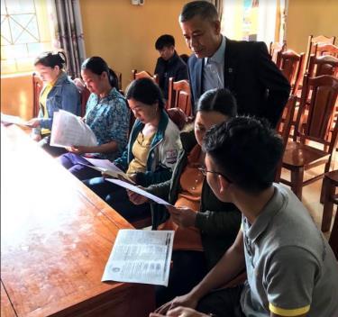 Cán bộ Bảo hiểm xã hội và Bưu điện huyện Trấn Yên phát tờ rơi cho người dân đến tham dự Hội nghị tuyên truyền về chính sách bảo hiểm xã hội tự nguyện.