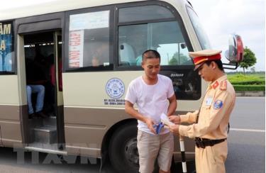 Cảnh sát giao thông kiểm tra phương tiện vận chuyển khách tại chốt giao thông.