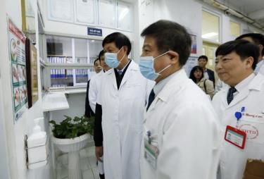 Thứ trưởng Đỗ Xuân Tuyên (trái) cùng đoàn công tác của Bộ Y tế kiểm tra công tác trực Tết và tặng quà cho một số bệnh nhân nặng điều trị tại bệnh viện Bệnh Nhiệt đới Trung ương.